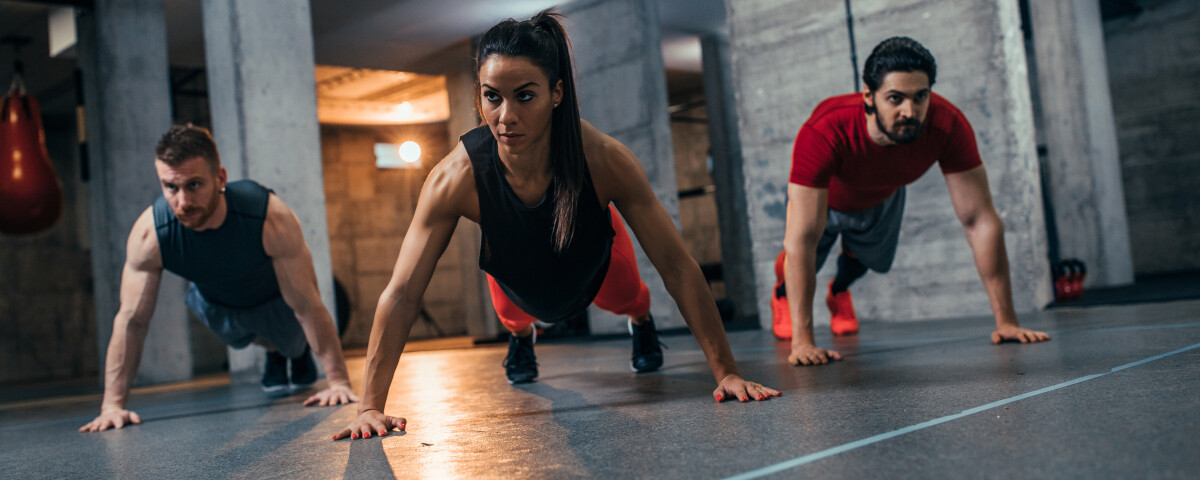 Shot of two young men and a woman standing in plank position at the gym